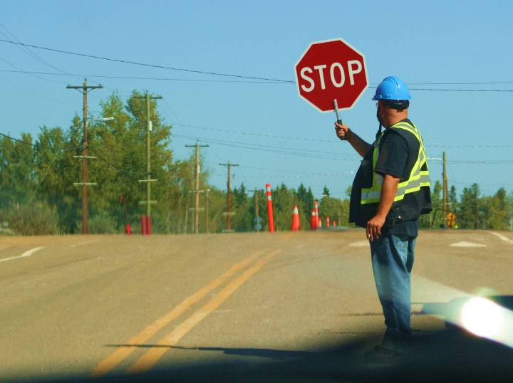 A flagman directs traffic on highway under construction